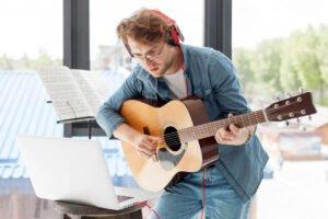 Man playing guitar and wearing headphones