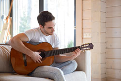 Man with guitar sitting on couch