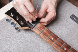 Master sets up the guitar neck anchor