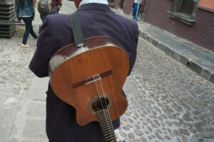 Rear view of a man with guitar on a street, san miguel de allende
