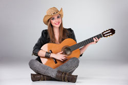 The beautiful woman in a cowboy's hat and acoustic guitar