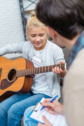 Young student learning how to strum guitar with fingers