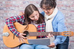 Young teenager learning to play the guitar with his teacher