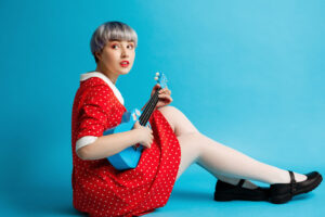 Close up portrait of beautiful dollish girl with short light violet hair wearing red dress holding ukulele